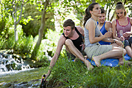 Italy, Tuscany, Friends with champagne sitting on grass and having picnic - HSIF000134