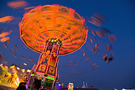 Germany, Munich, View of moving carousel at oktoberfest in night - HSIF000129