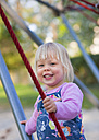 Germany, Munich, Girl climbing on climbing frame in playground, smiling, portrait - HSIF000126
