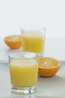 Glasses of orange juice with half oranges on table - ASF004411
