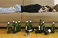 Germany, Hessen, Frankfurt, Drunk man lying on sofa with empty beer bottles - MUF001038