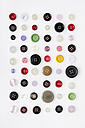 Colourful buttons arranged in row on white background - MUF001064