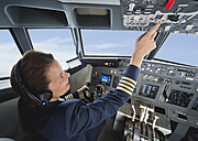 Germany, Bavaria, Munich, Woman flight captain piloting aeroplane from airplane cockpit - WESTF017036