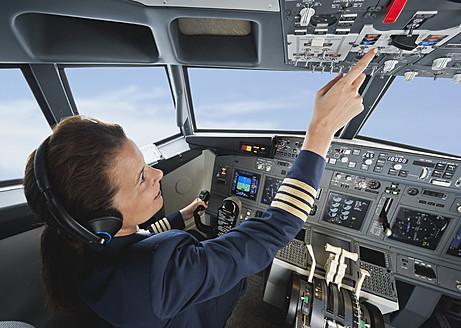 Germany, Bavaria, Munich, Woman flight captain piloting aeroplane from airplane cockpit - WESTF017036