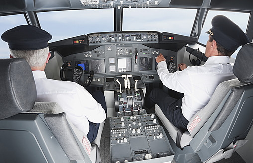 Germany, Bavaria, Munich, Pilot and co-pilot piloting aeroplane from airplane cockpit - WESTF017072