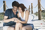 Spain, Majorca, Young couple with camera sitting on boardwalk at beach, smiling - WESTF017120