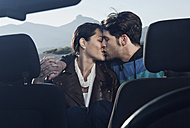 Spain, Majorca, Young couple kissing each other in cabriolet car, close up - WESTF017171