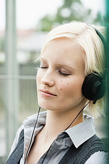 Germany, Bavaria, Munich, Young woman listening music - SPOF000051