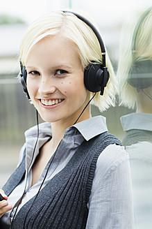 Germany, Bavaria, Munich, Young woman listening music, smiling, portrait - SPOF000052