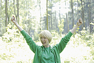 Germany, Bavaria, Schaeftlarn, Young woman in forest with arms up, portrait, smiling - TCF001780