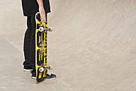 Germany, Duesseldorf, Man holding skateboard in public skate park - KJF000151