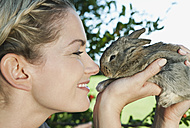 Italy, Tuscany, Young woman holding rabbit, close up - PDF000160