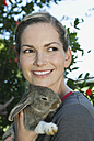 Italy, Tuscany, Young woman holding rabbit, close up - PDF000163