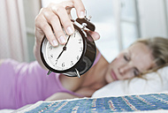 Italy, Tuscany, Young woman on bed turning off alarm clock in hotel room - PDF000236