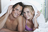 Italy, Tuscany, Young couple lying with bedsheet on bed in hotel room - PDF000255