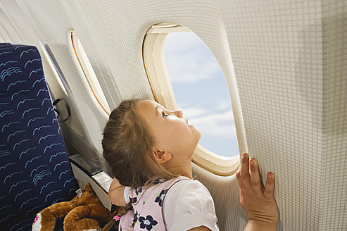 Germany, Munich, Bavaria, Girl looking through window in economy class airliner - WESTF017180