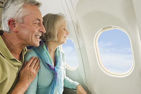 Germany, Munich, Bavaria, Senior couple looking out through window in economy class airliner - WESTF017228