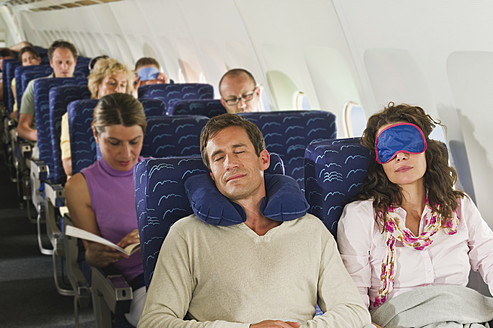Germany, Munich, Bavaria, Passengers sleeping in economy class airliner - WESTF017261