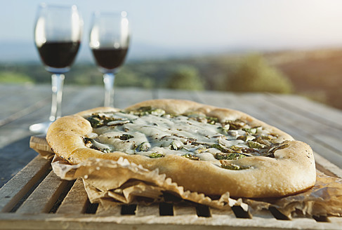 Italy, Tuscany, Magliano, Close up of pizza with wine glasses - WESTF017359