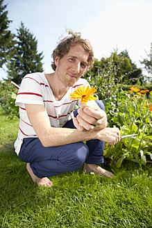 Germany, Hamburg, Man holding marigold in allotment garden - DBF000176