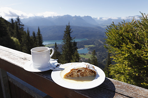 Germany, Bavaria, Upper Bavaria, Apple strudel and coffee cup on fence with mountains in background - SIEF001917