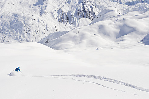 Austria, Zurs, Lech, Young man doing alpine skiing on Arlberg mountain - MIRF000288