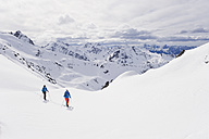 Austria, Stuben, Young couple doing telemark skiing on arlberg mountain - MIRF000300