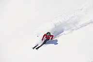 Austria, Zuers, Young man doing telemark skiing on Arlberg mountain - MIRF000336