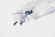 Austria, Zuers, Young man doing telemark skiing on Arlberg mountain - MIRF000345