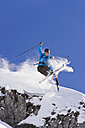 Austria, Zuers, Young man doing telemark skiing on Arlberg mountain - MIRF000348