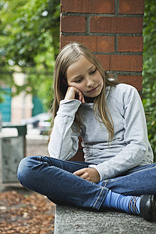 Germany, Berlin, Girl sitting in front of red brick wall - WESTF017473
