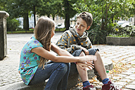 Germany, Berlin, Boy and girl sitting on curbstone - WESTF017491