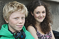 Germany, Berlin, Teenage couple with headphone, smiling - WESTF017524