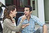Germany, Berlin, Couple eating snacks on sidewalk - WESTF017611