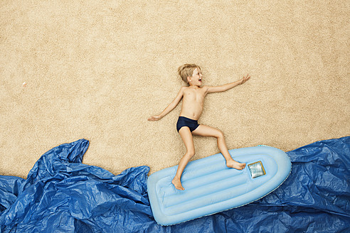 Germany, Boy on inflatable raft in water at beach - BAEF000280