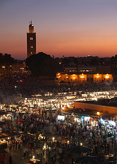 Morocco, Marrakesh, People at Djemaa el Fna square with Koutoubia Mosque at night - BSCF000061