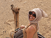 Morocco, Merzouga, Mature woman sitting on camel at Erg Chebbi desert - BSCF000069