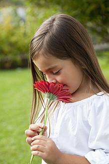 Germany, Bavaria, Huglfing, Girl with flower in garden, smiling - RIMF000022