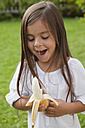 Germany, Bavaria, Huglfing, Girl with banana in garden, smiling - RIMF000021