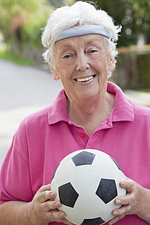 Germany, Bavaria, Huglfing, Senior woman holding soccer ball, smiling, portrait - RIMF000015
