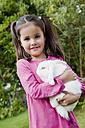 Germany, Bavaria, Huglfing, Girl holding rabbit in garden, smiling, portrait - RIMF000007