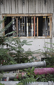 Germany, Berlin, Water pipes and wet wall on construction site - JMF000070