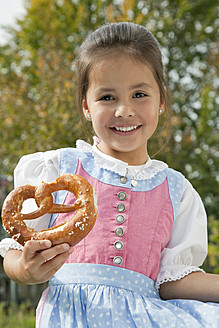 Germany, Bavaria, Huglfing, Girl holding pretzel in garden, smiling, portrait - RIMF000037