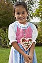 Germany, Bavaria, Huglfing, Girl with gingerbread heart in garden, smiling, portrait - RIMF000042
