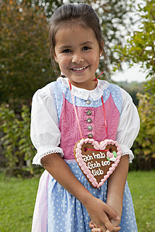 Germany, Bavaria, Huglfing, Girl with gingerbread heart in garden, smiling, portrait - RIMF000042