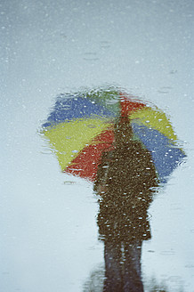 Germany, Bavaria, Huglfing, Young woman with umbrella reflecting in water puddle - RIMF000044