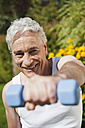 Germany, Bavaria, Mature man doing exercise with dumbbells - WESTF017624