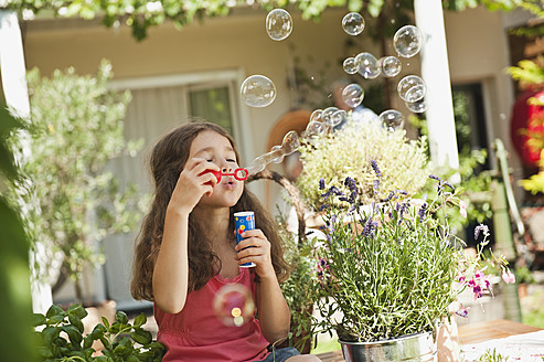 Germany, Bavaria, Girl blowing soap bubbles in garden - WESTF017699