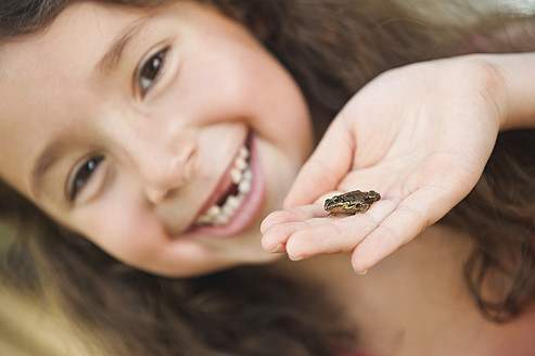 Germany, Bavaria, Human hand with little frog, girl smiling in background - WESTF017714