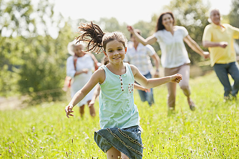 Germany, Bavaria, Family running together in grass at picnic - WESTF017776